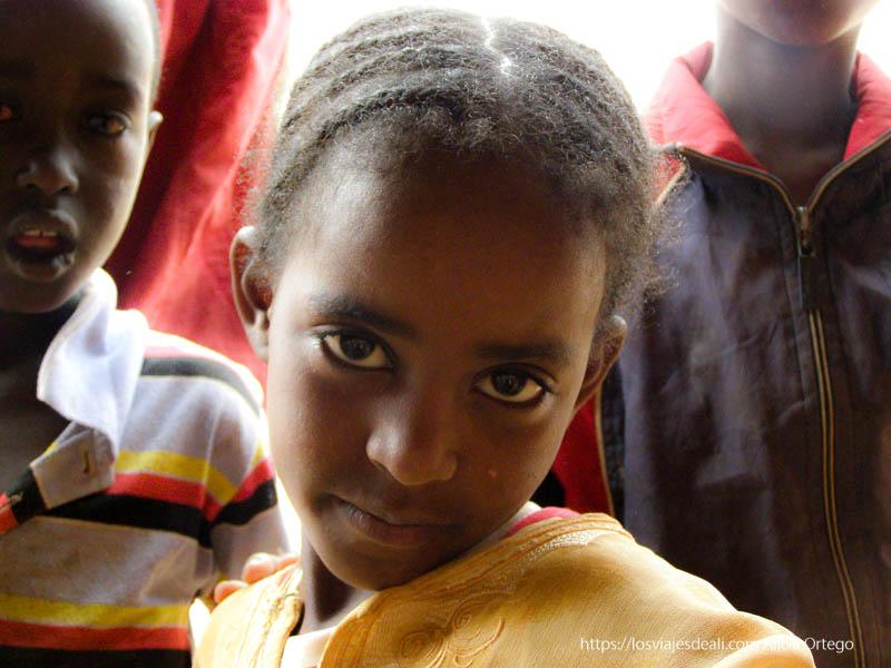 niña con ojos negros en forma de almendra y trencitas el sod