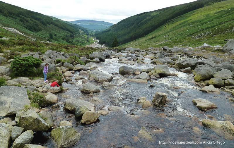 río bajando entre montañas y dos niñas jugando en la orilla glendalough