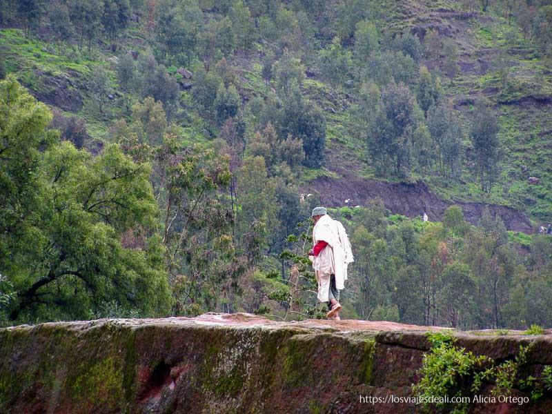 peregrino andando por la roca con montaña detrás iglesias de lalibela
