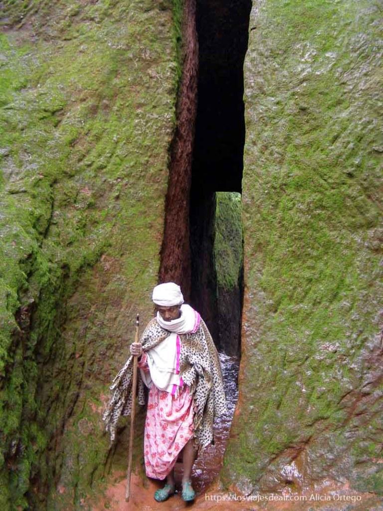 cura etíope saliendo de pasillo estrecho y muy alto excavado en la roca iglesias lalibela