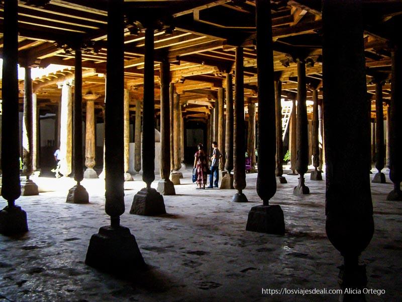 mezquita llena de columnas de madera en khiva