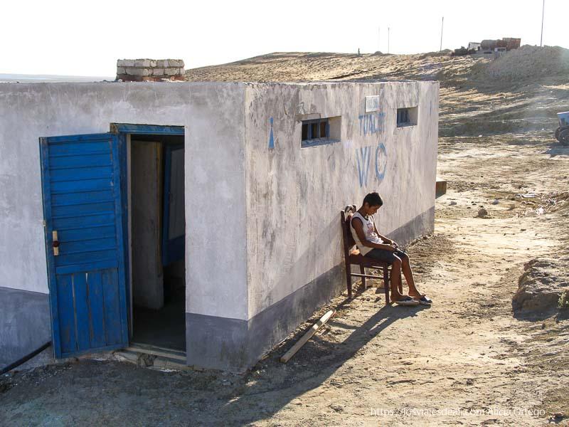 caseta de wc con niño sentado al sol khiva