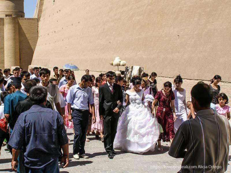 novios andando con invitados junto a la muralla de khiva