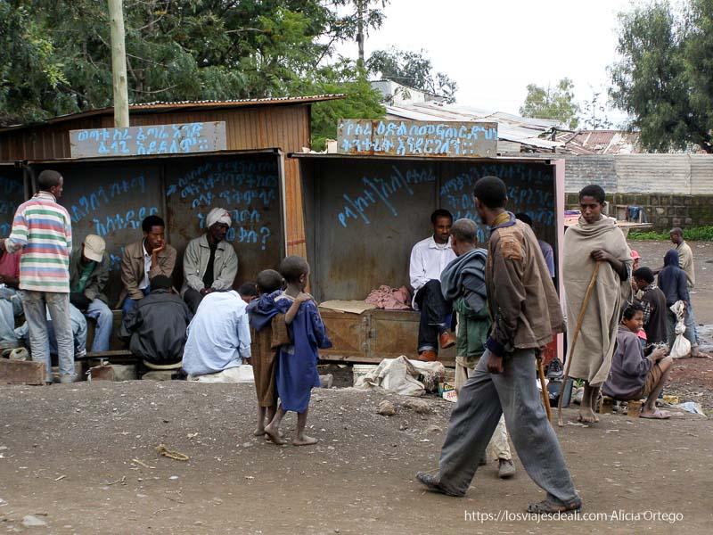 hombres limpiándose los zapatos en casetas de chapa en lalibela