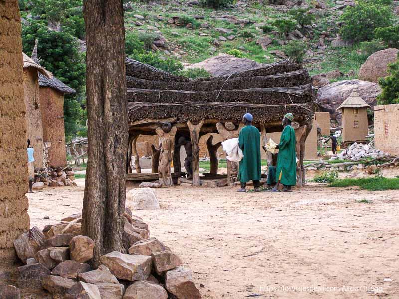hombres vestidos de verde junto a la casa de la palabra pais dogon