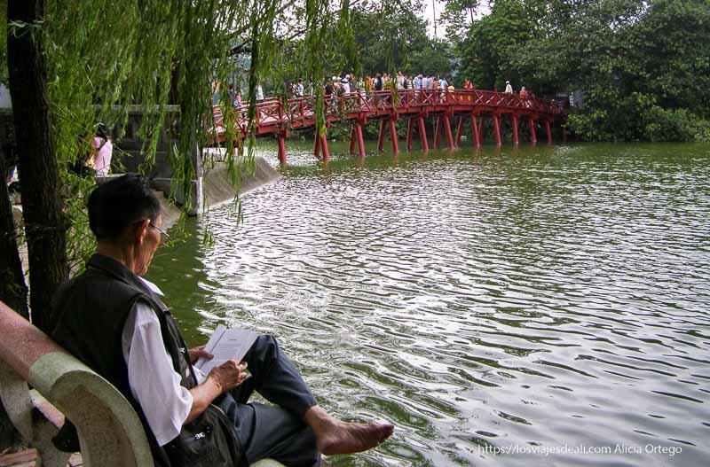 lago con puente rojo y señor leyendo en un banco qué ver en hanoi