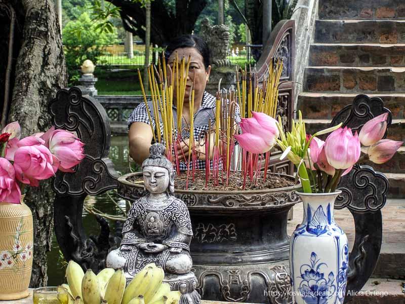 mujer poniendo varitas de incienso en templo qué ver en hanoi