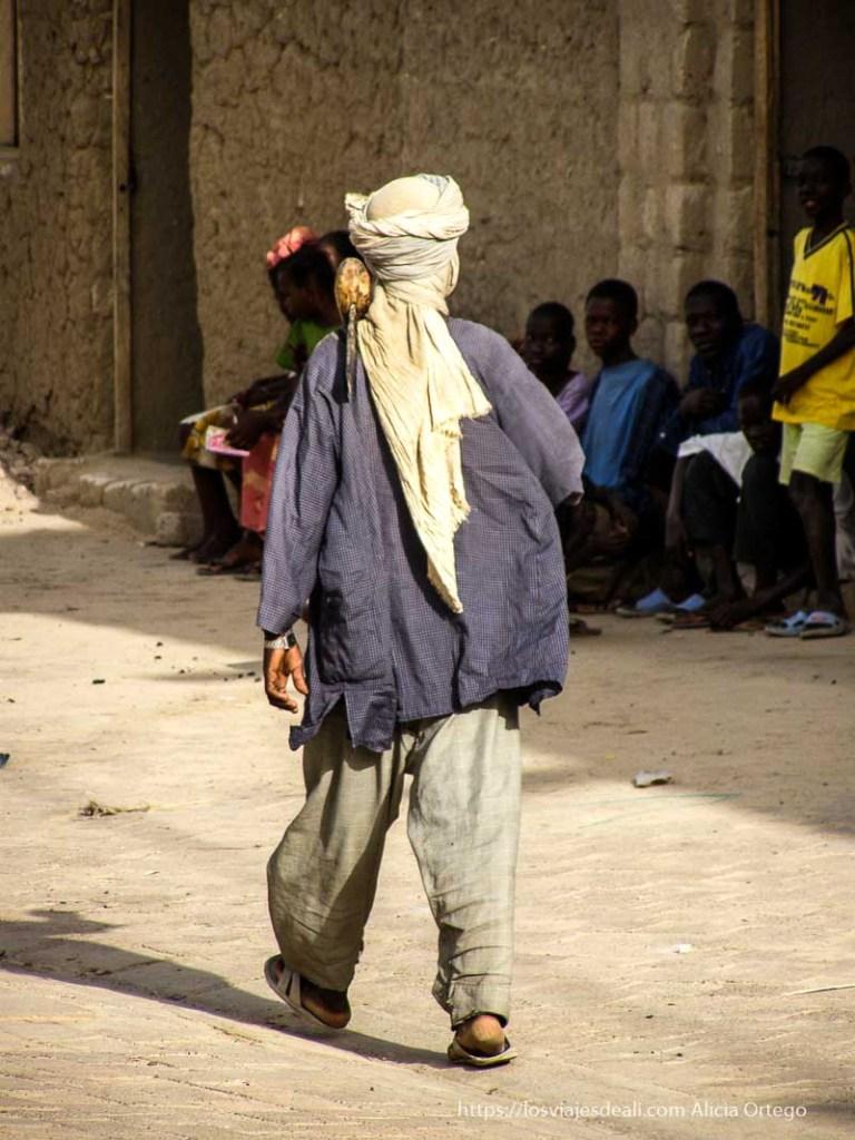 hombre andando con hacha neolítica al hombro en tombuctú