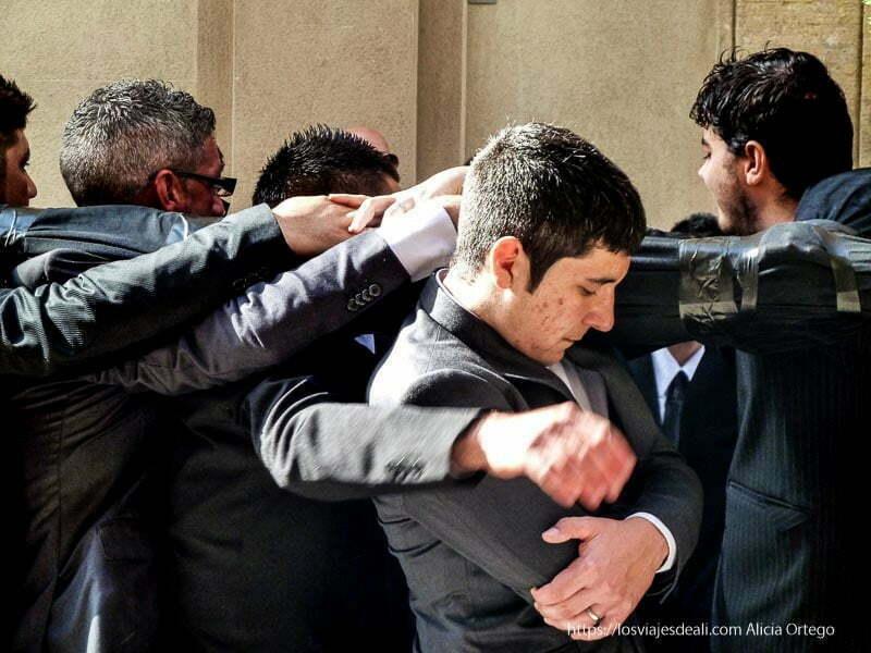 hombres llevando un paso el protagonista en posición de rezo Trapani en semana santa