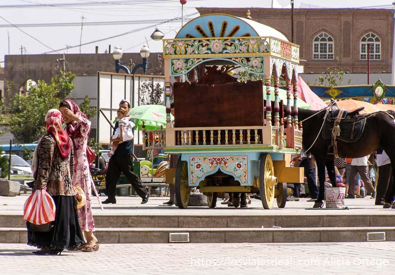 carro de madera pintado de colores con dos mujeres pasando delante kashgar en la ruta de la seda