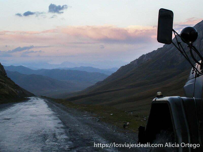bajando al atardecer por carretera de montaña con nubes rosas campo base del pico lenin