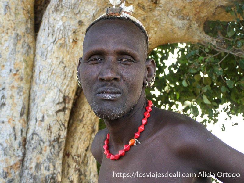 retrato de hombre dasanech con collar rojo y muchos pendientes en las dos orejas