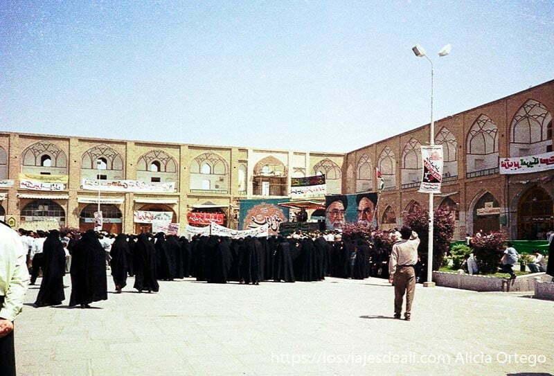 mujeres de negro en la plaza de isfahan manifestándose ante carteles de jomeini