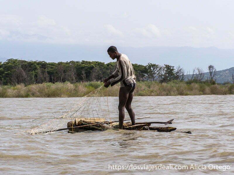 pescador en minibarca de madera con su red en el lago chamo