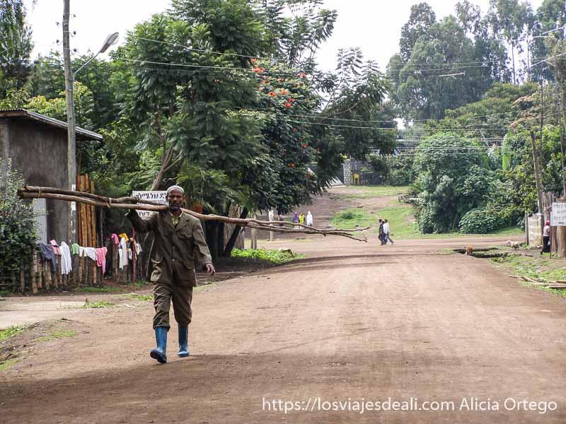 hombre llevando dos ramas larguísimas al hombro en un pueblo de camino al lago chamo