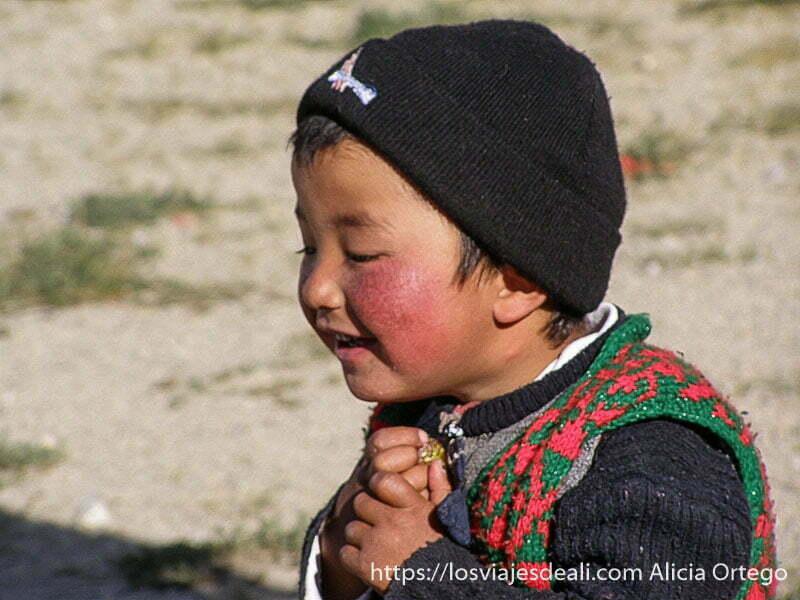 niño con mejillas rojas cortadas por el frío junto al lago karakul