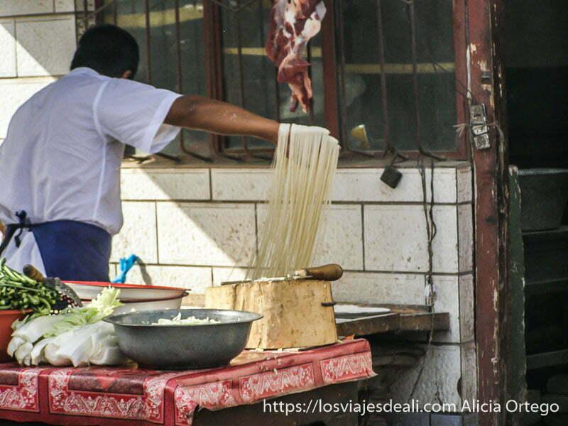 hombre haciendo fideoos con las manos mercado de Kashgar