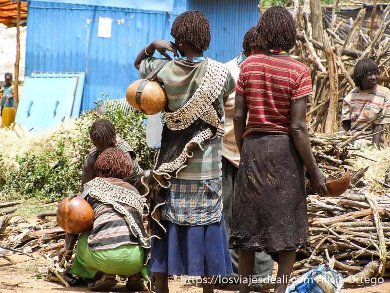 mujeres de espaldas con calabazas al hombro y tiras de conchas de decoración