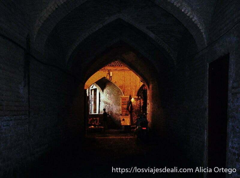 pasillo oscuro con arcos de ladrillo y al fondo luz rojiza en bazar de shiraz
