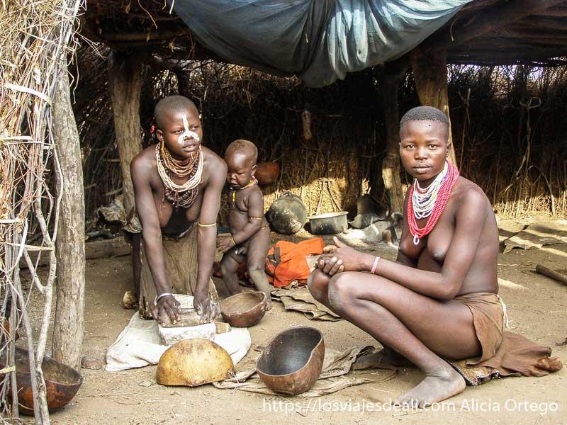 dos mujeres de la tribu karo una moliendo grano en molino neolítico y con bebé junto a ella