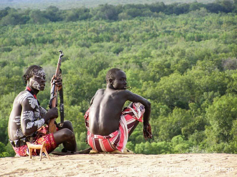 dos jóvenes de la tribu karo uno de ellos con dibujos blancos en el cuerpo y la cara y con un rifle en la mano