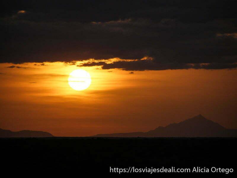 atardecer con el sol como gran bola amarilla y montaña