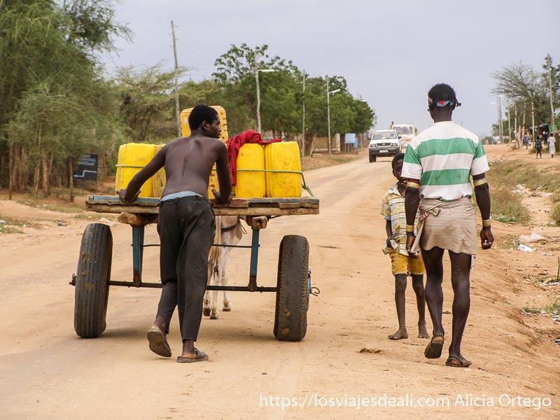 un hombre empujando un carro lleno de bidones de color amarillo y al lado un hamer caminando turmi