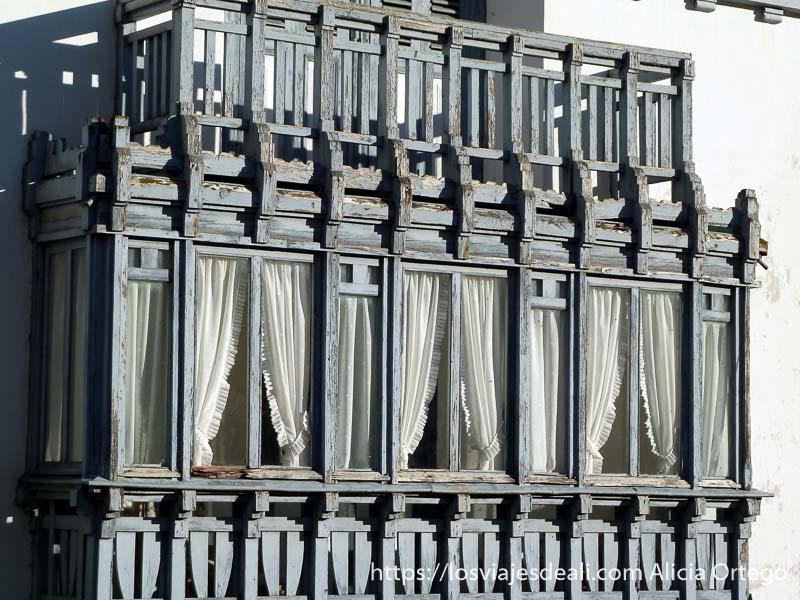 balcón de madera con visillos