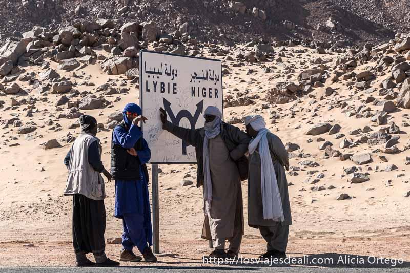 guías tuareg junto al cartel que indica dirección a Libia y Níger