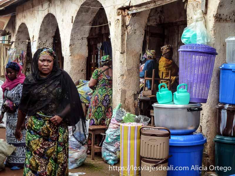 mujeres en una calle de foumban entre tiendas bajo soportales