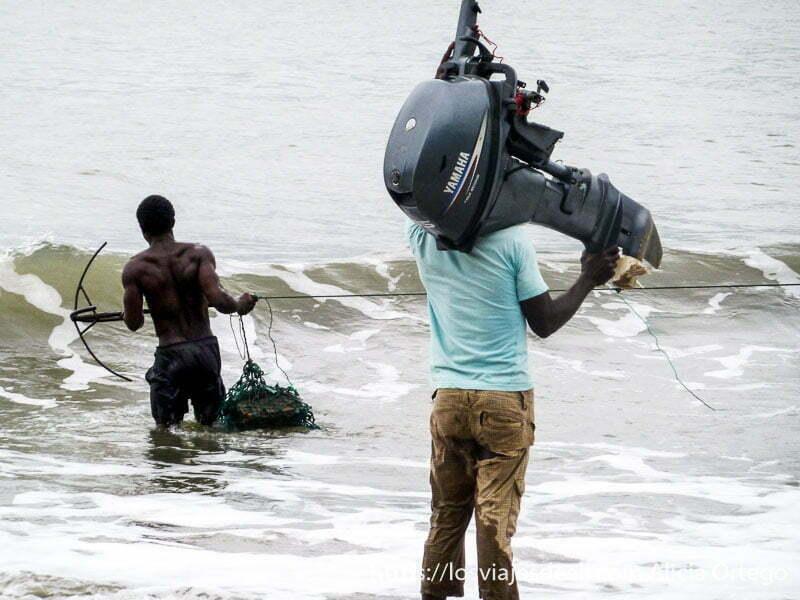 hombre sosteniendo motor de barca en el hombro en londji