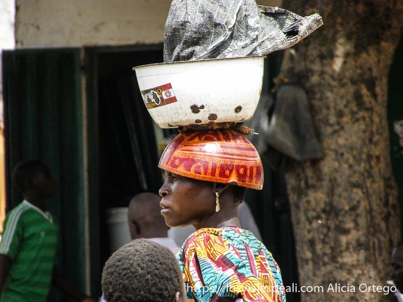mujer con calabaza decorada como sombrero y palangana encima mercado de tourou