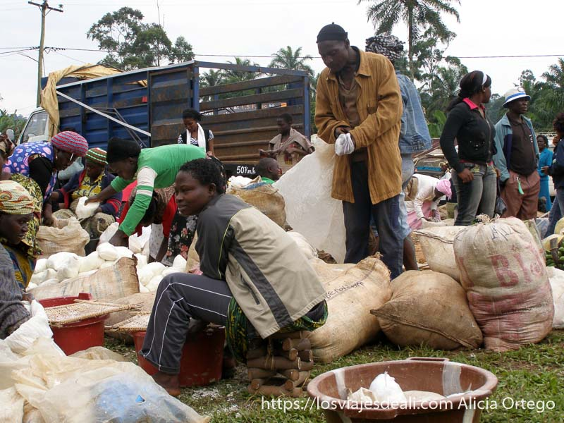 mujer rodeada de sacos y clientes en mercado de bafut montes bamileké