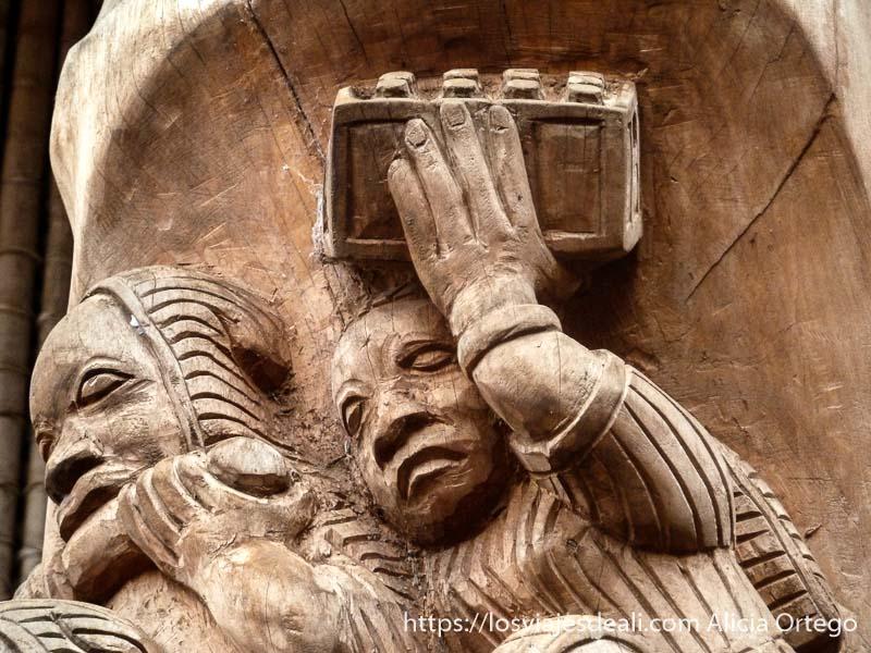 relieve en madera de hombre llevando caja de cervezas