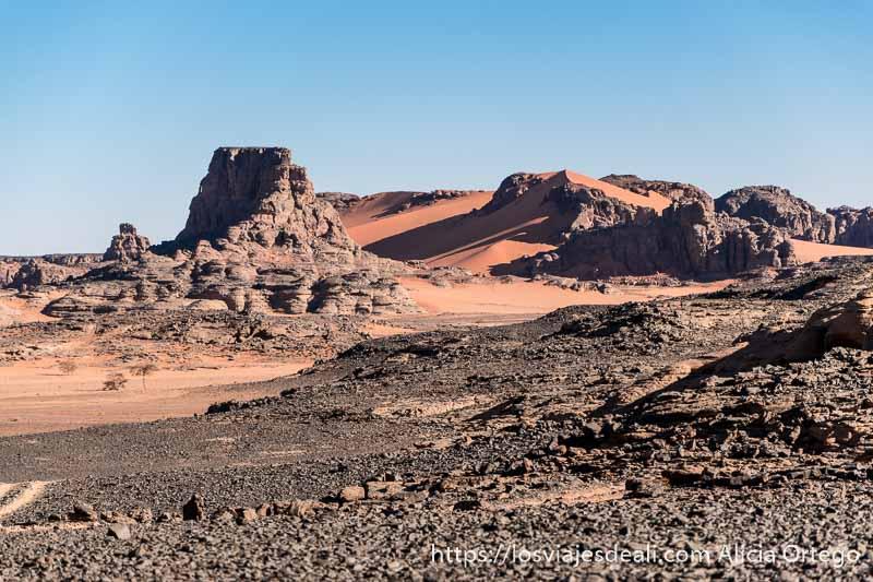 paisaje del tadrart con torres de piedra entre dunas de color naranja y cielo azul