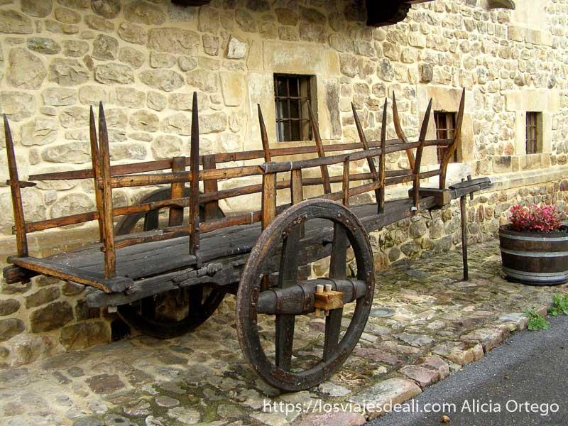 antiguo carro de madera junto a un muro de piedra con ventanas pequeñas en Renedo