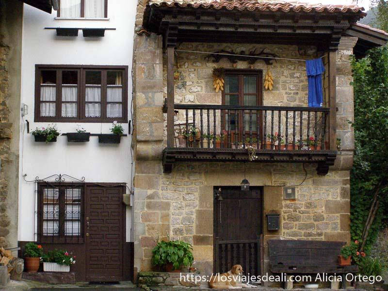 casa tradicional con balcón de madera, mazorcas colgadas en la pared y perro en la puerta