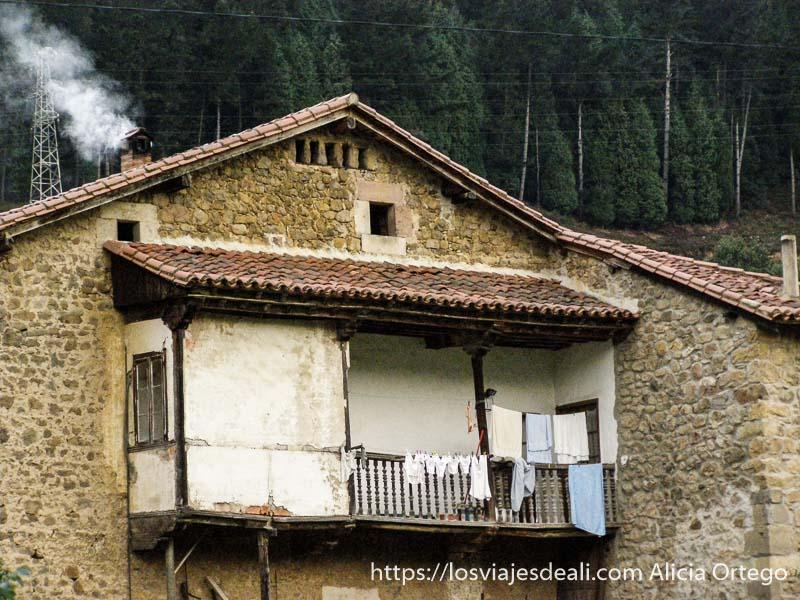 casa de piedra con balcón de madera medio tapado con yeso junto al parque natural saja besaya