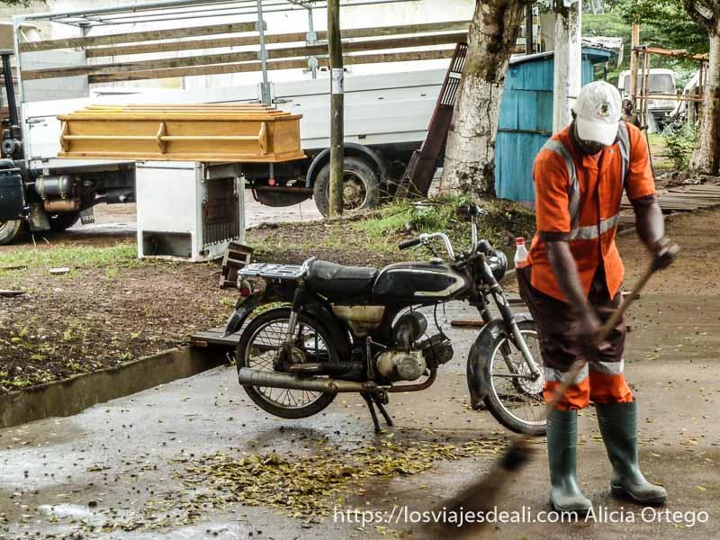 señor barriendo la calle con uniforme naranja y detrás un ataúd sur de camerún kribi