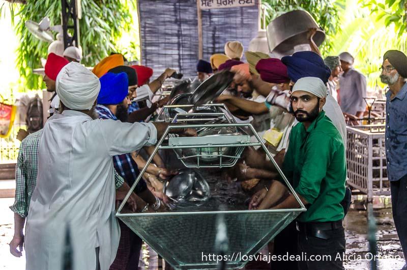 hombres fregando platos en el templo dorado de los sijs