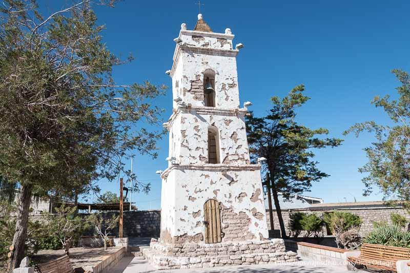 campanario de iglesia de toconao con tres niveles y pintada de blanco atacama