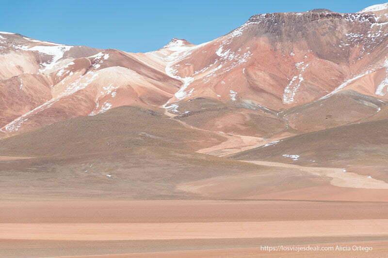 montañas de colores rojizos y salpicadas de nieve con cielo azul desierto de dalí bolivia