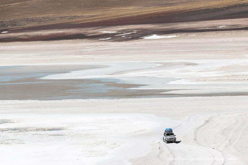 coche 4x4 circulando por pista junto a laguna andina en bolivia