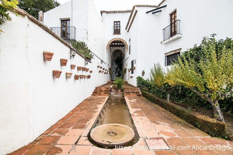 rincón del patio del palacio de mondragón con fuente y canal para el agua y muros blancos