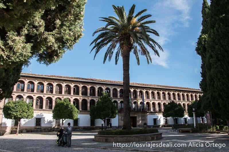 fachada del ayuntamiento con arcos y balcones y una palmera en el centro de la plaza escapada a ronda