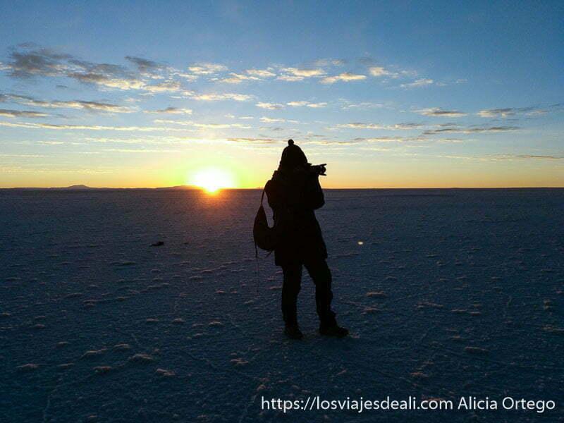 yo haciendo foto con el sol detrás saliendo por el horizonte en el amanecer en el salar de uyuni