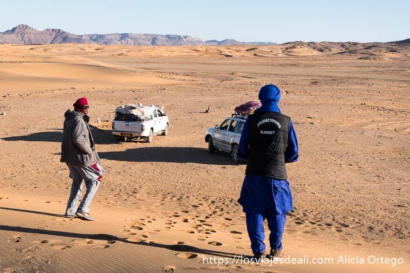 dos tuareg bajando por una duna hacia los coches 4x4 consejos para viajar a argelia