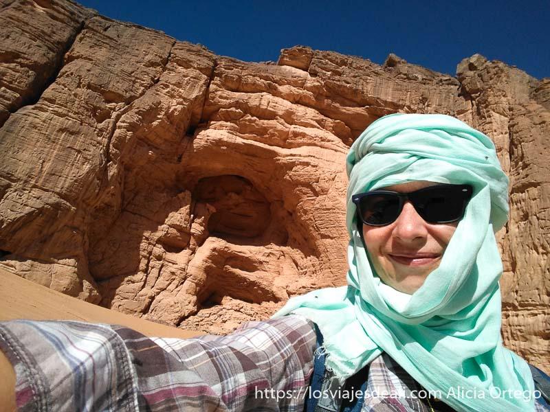 selfie con mi turbante azul y gran cueva detrás en el sahara consejos para viajar a argelia