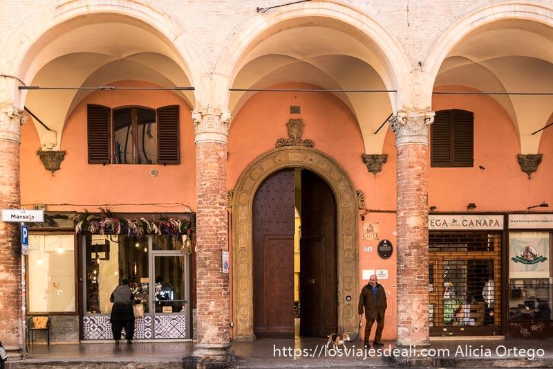 calle porticada con gran portal y un hombre paseando a su perro en bolonia