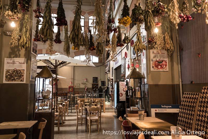 restaurante con ramos de flores y hierbas colgados del techo boca abajo sobre las mesas